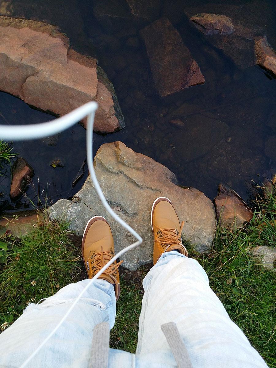 Feet and headphone cord by the water